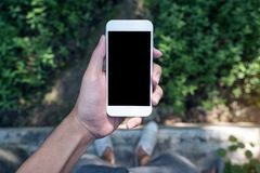 Mockup image of a man`s hand holding white mobile phone with blank black screen while standing on concrete polishing floor with gr. Een leave and nature stock image