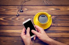 Mockup image of a mobile phone with an empty black screen and coffee in a yellow cup on an old wooden table in a cafe Stock Images