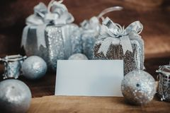 Mockup image of white blank name card with silver christmas decorations. On vintage wooden background Stock Image