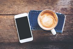 Mockup image of white mobile phone with blank black screen and hot latte coffee. On vintage wood table in cafe Stock Photo
