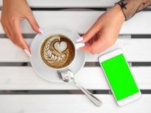 Mockup image of white mobile phone with green screen and hand holding phone. coffee on the table. royalty free stock images