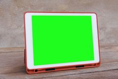 Mockup image of  White tablet pc with blank green desktop screen on wooden table