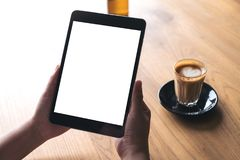 A woman holding black tablet pc with white blank screen with coffee cup on table background. Mockup image of a woman holding black tablet pc with white blank Stock Image