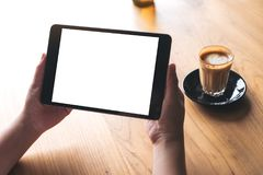 A woman holding black tablet pc with white blank screen with coffee cup on table background. Mockup image of a woman holding black tablet pc with white blank Royalty Free Stock Image