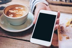 A woman holding and showing white mobile phone with blank black screen and latte coffee cup and snack on wooden table in cafe. Mockup image of a woman holding Stock Images