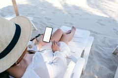 A woman holding white mobile phone with blank desktop screen while laying down on beach chair on the beach royalty free stock images