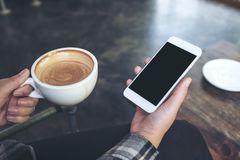 A woman`s hand holding white mobile phone with blank black desktop screen and coffee cup in cafe. Mockup image of a woman`s hand holding white mobile phone with Stock Photography