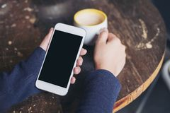 Mockup image of woman`s hands holding white mobile phone with blank black screen and a coffee cup on wooden table. In vintage cafe Stock Image