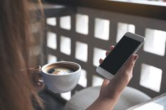 Woman`s hands holding white mobile phone with blank black screen while drinking coffee in cafe. Mockup image of woman`s hands holding white mobile phone with Royalty Free Stock Photo