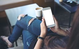 Woman`s hands holding white mobile phone with blank screen on thigh in cafe stock photos
