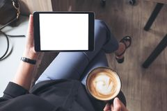 A woman sitting cross legged and holding black tablet pc with blank white desktop screen while drinking coffee in cafe. Mockup image of a woman sitting cross Royalty Free Stock Images
