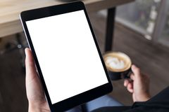 A woman sitting cross legged and holding black tablet pc with blank white desktop screen while drinking coffee in cafe. Mockup image of a woman sitting cross Stock Image