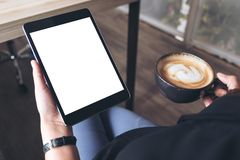 A woman sitting cross legged and holding black tablet pc with blank white desktop screen while drinking coffee in cafe. Mockup image of a woman sitting cross Stock Photography