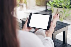 Mockup image of a woman sitting and holding black tablet pc with blank white desktop screen , feeling relaxed with sand and beach stock image