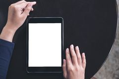 Mockup image of a woman using black tablet pc with blank white screen. On a black table background Royalty Free Stock Photo