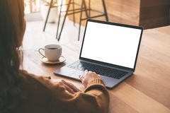 A woman using and touching on laptop touchpad with blank white desktop screen with coffee cup on wooden table stock photography