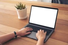 A woman using and typing on laptop with blank white screen on wooden table royalty free stock image