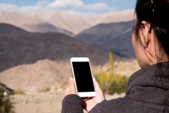 Mockup image of a woman using white mobile phone with blank black screen while standing in front of mountain. And blue sky Stock Image