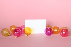 Mockup with invitation card on light pink background with christmas ornaments. Royalty Free Stock Photo