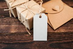 Mockup kraft gift boxes with tag on wooden background Stock Photo