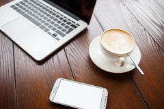Mockup with laptop and smartphone on table in cafe stock photography