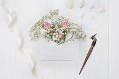 Mockup list z kwiatami i kaligraficzny pióra kartka z pozdrowieniami dla St walentynki ` s dnia w wieśniaku projektujemy z miejsc zdjęcia stock