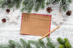 Mockup for new year 2018. Sheet of kraft paper near spruce branches, pine cone on light wooden background top view Stock Photos