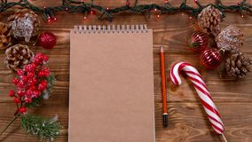 Mockup Notebook and pencil lie on the table, Christmas toys and garlands around. Top view. Notebook and pencil lie on a wooden table, lollipop, Christmas toys stock video