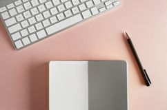Mockup Of Paper Note Book, Computer Keyboard On Empty Color Desk. Business Empty Mock-up Background For Message Writing Royalty Free Stock Image