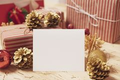 Mockup paper card with golden pine cones christmas and gift box royalty free stock photography
