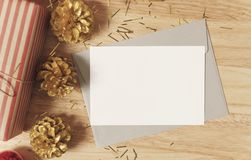 Mockup paper card with golden pine cones christmas and gift box royalty free stock photo