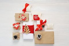 Mockup paper parcels wrapped tied with tags. A red heart and some christmas gift boxes wrapped with paper kraft and tied. With red and white bakers twine on a stock photo