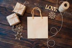 Mockup Papierowa torba od Kraft papieru i boże narodzenie prezenta pudełek na drewnianym tle Zdjęcie Stock
