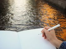 Mockup of person`s hand holding blank white notebook preparing to write down his or hers ideas. stock photos