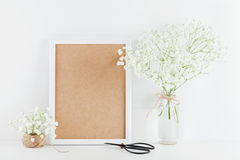 Mockup of picture frame decorated gypsophila flowers in vase on white working desk with clean space for text and design your blogg