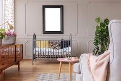 Mockup plakat nad kołyska w popielatym dziecko sypialni wnętrzu z stołem i karłem Istna fotografia obraz royalty free