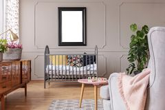 Mockup of poster above cradle in grey child`s bedroom interior with table and armchair. Real photo. Mockup of poster above cradle in grey child`s bedroom royalty free stock image