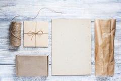Mockup pudełka prezenty z naturalnym papierem, kopertą i floss na drewnianym stole, odgórny widok, miejsce dla twój teksta i rysu zdjęcie royalty free