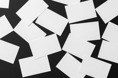 Mockup of scattered white business cards stacks arranged in rows. At black textured paper background Stock Photo