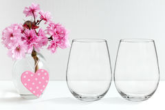 Mockup - stemless wine glasses, blossom in a vase. Floral mock-up of two stemless wine glasses, perfect for businesses who sell decals, vinyl stickers, just royalty free stock images