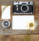 Mockup stillife with retro photo, camera, lens and pressed plant Royalty Free Stock Photo