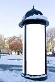 Mockup street advertising or information column stand on sidewalk at winter Royalty Free Stock Photo