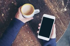 Mockup top view image of woman`s hands holding white mobile phone with blank black screen and a coffee cup on wooden table. In vintage cafe Stock Image