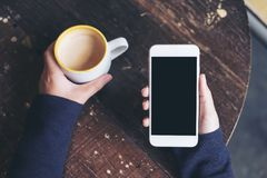 Mockup top view image of woman`s hands holding white mobile phone with blank black screen and a coffee cup on wooden table. In vintage cafe Stock Photos