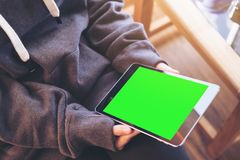 Mockup top view image of a woman sitting cross legged and holding black tablet pc with blank green screen on thigh. And wooden floor background Royalty Free Stock Photos