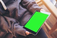 Mockup top view image of a woman sitting cross legged and holding black tablet pc with blank green screen on thigh Royalty Free Stock Photos