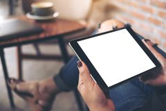 Mockup top view image of a woman wearing ripped jean sitting cross legged , holding black tablet pc with blank white desktop scree. N on thigh in cafe Stock Images