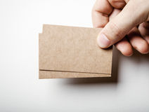 Mockup of two craft business cards and mans hand. Mock up of two blank kraft business cards holding in a mans hand on the white background Stock Image