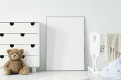 Mockup of white empty poster between cradle and teddy bear in ki royalty free stock images