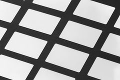 Mockup of white gift plastic cards arranged in rows at black pap Stock Photo
